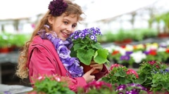 Girl in a pink jacket holding flower pot with cineraria Stock Footage