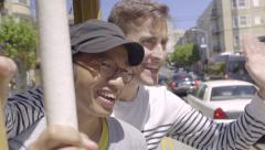 Happy Gay Couple Ride Trolley Through San Francisco, They Wave To People(4K) Stock Footage