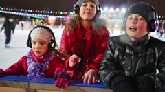 Happy family have fun on the silent disco skating near fencing Stock Footage