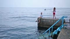 Little sister is going to her brother in pier near the sea. Stock Footage