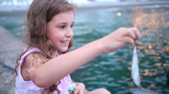 Curly cute girl is looking at the caught small fish. Stock Footage