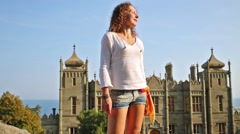 Woman with shorts and shirt is standing in front of Palace. Stock Footage