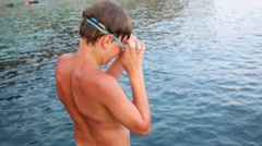 Boy is putting on his goggles and jumping to the water. Stock Footage