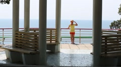 Young woman is standing on the balcony and gazing to sea. Stock Footage