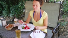 Woman is sitting at the rocking-table and eating strawberries. Stock Footage
