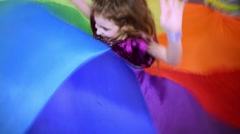 Little girl jumps in the center of  waving cloth ring. - stock footage