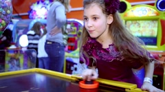 Little girl in suit plays air hockey at amusement playground. Stock Footage