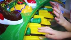 Little girls play on child game machine at amusement playground. Stock Footage