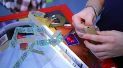 Boy gathers tickets from gaming table at amusement playground. Stock Footage