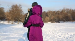 Boy and girl whirl holding hands at snowy glade on winter day. Stock Footage