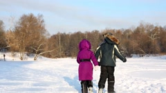 Boy and girl run by snowy glade on bright winter day, rear view. Stock Footage