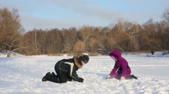 Boy and girl sit on ground, throwing snow at each other. Stock Footage