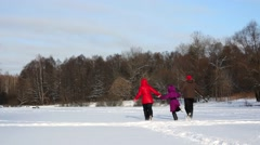 Family runs there and back holding hands across snowy glade Stock Footage