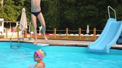 Little boy jumps in swimming pool to his sister from poolside. Stock Footage