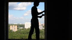 Silhouette of worker with spatula who cleans window aperture Stock Footage