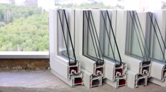 Six  samples of PVC windows stand on a concrete windowsill in room Stock Footage