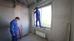 Two workers install window frame and check vertical accuracy Stock Footage