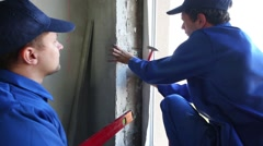 Worker hammers dowel fixing bracket on jamb. Another one stands near Stock Footage