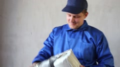 Worker inspects roll of insulation foiled tape for windows. Stock Footage