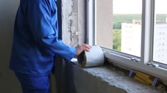 Worker unroll insulation foiled tape for windows at windowsill. Stock Footage