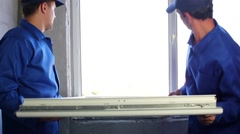 Two workers put window sash into new installed frame. - stock footage