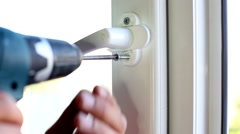 Male hands fasten window handle by electric screwdriver. Stock Footage