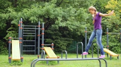 Stock Video Footage of girl goes balancing by parallel metal bars and then jumps  down