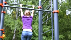 Stock Video Footage of girl swings on horizontal bar and jumps down at sports ground