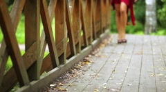 Legs of girl dressed in red suit walking along bridge at park Stock Footage