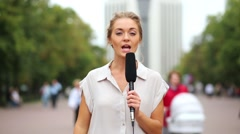 girl with microphone stands, then turns and begins speak. - stock footage