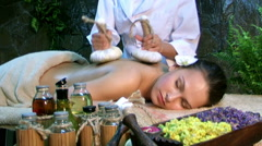 Woman getting thai herbal compress massage in spa - stock footage