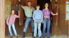 Family dressed like cowboys stands on porch at saloon door. Stock Footage