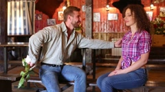 Man gives woman bunch of flowers while they sit at pub Stock Footage