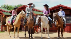 Cowboy family on horsback against wooden pavilions Stock Footage