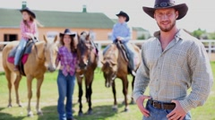 Man in cowboy hat stands foreground, looks back to his family. Stock Footage