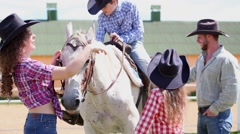 Boy sits on horseback, his mother, father and sister stand near. Stock Footage