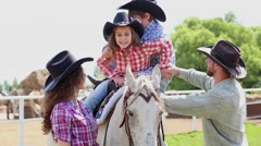 Boy gets off horse, parents help him, holding horses bridles. Stock Footage