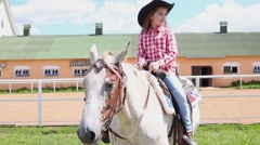 Little girl in cowboy hat sits on horseback against squat building Stock Footage