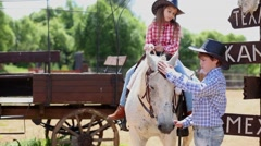 Boy holds by the bridle a horse, on which girl sits. Stock Footage
