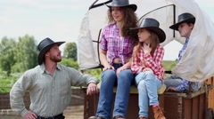 Cowboy family sits on wagon, then begins to get off. Stock Footage
