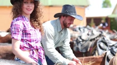 Woman and man in cowboy hats feed horses with hay. - stock footage