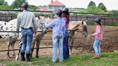 Cowboy family stands at metal fence of paddock with horses. Stock Footage