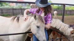 Curly woman stands at metal fence of paddock and strokes horse. Stock Footage