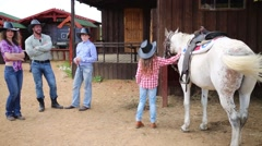 Cowboy family of four stands on square against trading pavilions. Stock Footage