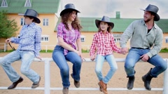 Cowboy family of four sits on metal fence against squat building. Stock Footage