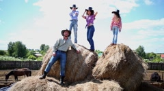 Cowboy family of four stands on big dried hay bales. Stock Footage