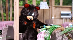 Stock Video Footage of Actor dressed in bear suit imitates drinking beverage at cafe