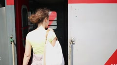 Young woman with curly hair enters train car and waves a farewell Stock Footage