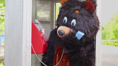 Actor dressed in bear suit talks phone in call box at park. Stock Footage