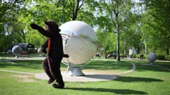 Actor dressed as bear moves backwards and waves his paws at lawn Stock Footage